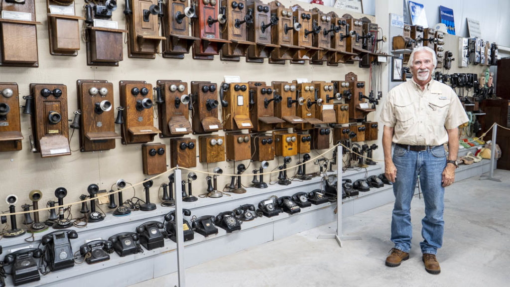 Art Peters standing in front of a collection of telephones at the Hinton Historical Museum - photo by Dennis Spielman